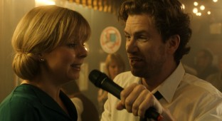 Anne (Lene Maria Christensen) og Gordon Dennis (Nikolaj Lie Kaas) midt i en næsten ceremoniel karaoke. Photo courtesy of Blenkov & Schønnemann Pictures og Nordisk Film Biografdistribution.